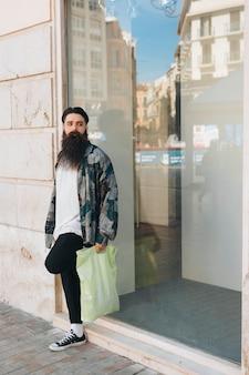 Portrait, debout, dehors, magasin, tenue, plastique, sac, main