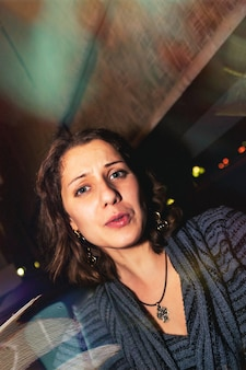 Portrait décontracté d'une jeune femme émotionnelle positive dans un club de restaurant de nuit à table. concept de mode de vie de la ville de nuit. espace de copie