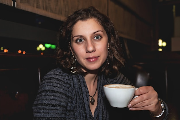 Portrait décontracté d'une jeune femme émotionnelle positive avec une tasse de café dans un club de restaurant de nuit à table. concept de mode de vie de la ville de nuit. espace de copie