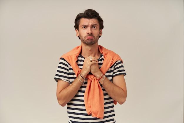 Portrait de demander à un homme aux cheveux et soies brune. porter un t-shirt rayé, un pull noué sur les épaules. bouche les lèvres et plaide, paumes ensemble