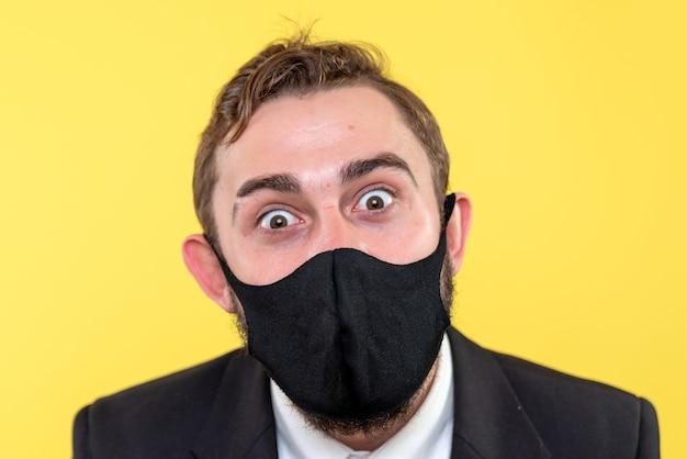 Portrait de demi-corps d'homme d'affaires avec des yeux heureux sur jaune