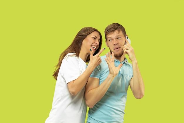 Portrait de demi-longueur de beau jeune couple isolé. l'homme parle au téléphone, la femme est en colère pour cela. expression faciale, concept d'émotions humaines. couleurs à la mode.