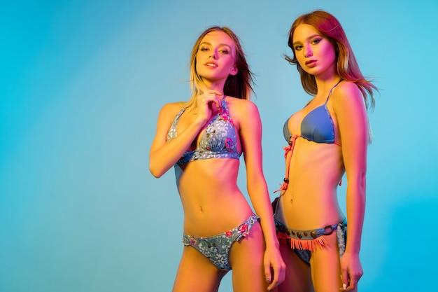 Portrait demi-longueur de belles jeunes filles isolé sur fond bleu studio à la lumière du néon. femmes posant en body à la mode. expression faciale, été, concept de week-end. couleurs tendance.