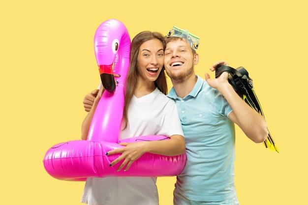 Portrait demi-longueur du beau jeune couple sur l'espace jaune. femme et homme debout avec anneau de natation rose comme un flamant rose et des palmes