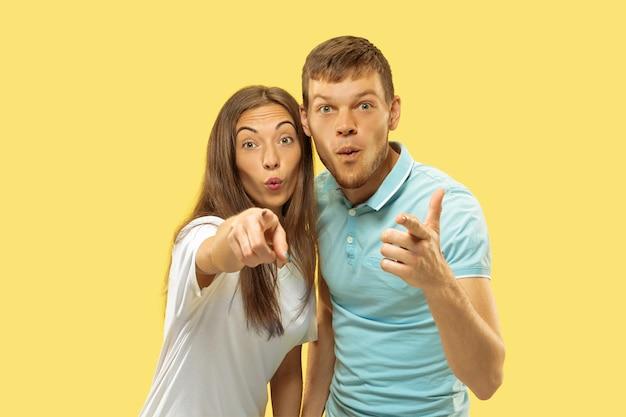 Portrait demi-longueur du beau jeune couple sur jaune