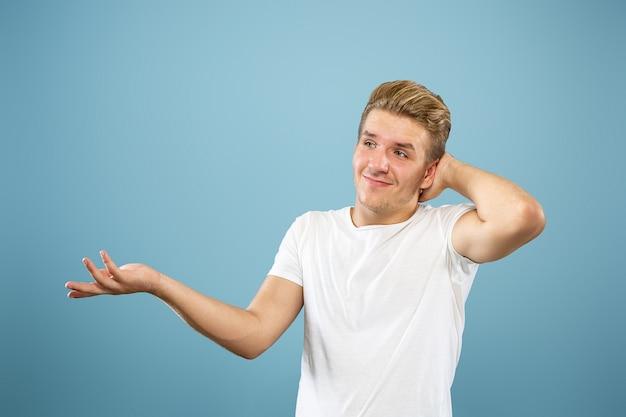 Portrait demi-longueur du jeune homme caucasien sur fond bleu studio. beau modèle masculin en chemise. concept d'émotions humaines, expression faciale, ventes, publicité. montrer, semble incertain, copyspace.