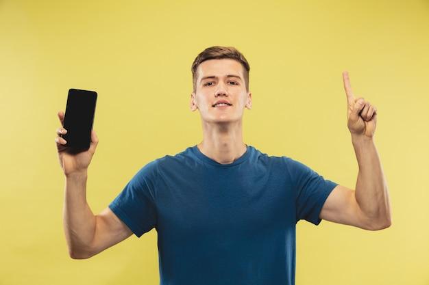 Portrait demi-longueur du jeune homme caucasien sur fond de studio jaune. beau modèle masculin en chemise bleue. concept d'émotions humaines, expression faciale. affichage de l'écran du téléphone et pointant vers le haut.