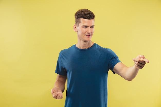 Portrait demi-longueur du jeune homme caucasien sur fond de studio jaune. beau modèle masculin en chemise bleue. concept d'émotions humaines, expression faciale. montrer et pointer quelque chose. attrayant.