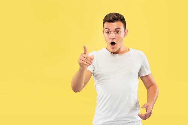 Portrait demi-longueur du jeune homme caucasien sur fond de studio jaune. beau modèle masculin en chemise. concept d'émotions humaines, expression faciale, ventes, publicité. toucher une barre de recherche vide.