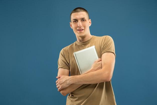 Portrait demi-longueur du jeune homme caucasien sur studio bleu