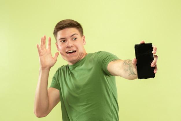 Portrait demi-longueur du jeune homme caucasien sur studio vert