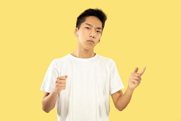 Portrait demi-longueur du jeune homme coréen sur fond de studio jaune. modèle masculin en chemise blanche. tenir et inviter. concept d'émotions humaines, expression faciale. vue de face. couleurs à la mode.