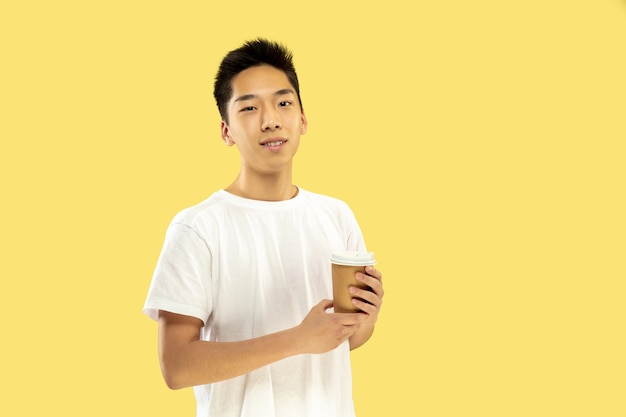 Portrait demi-longueur du jeune homme coréen sur jaune