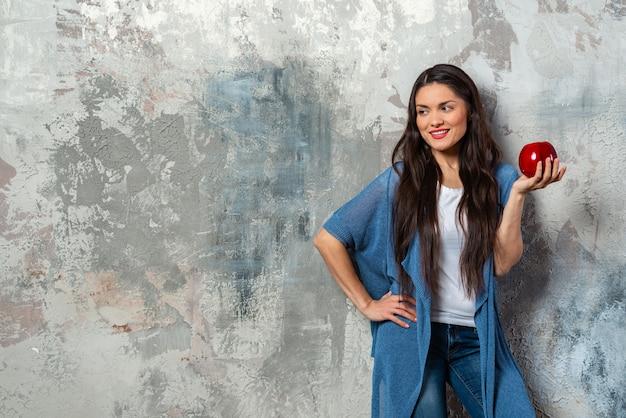 Portrait, demi-longueur, de, femme brune, tenant, grosse, pomme rouge, dans, sa, main