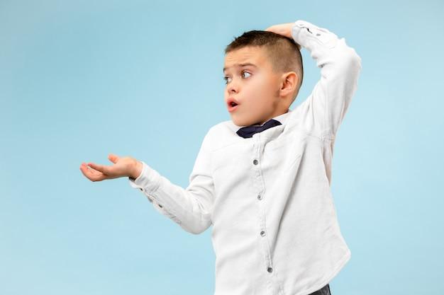 Portrait demi-longueur garçon isolé sur fond de studio bleu à la mode. jeune adolescent surpris, frustré et déconcerté.