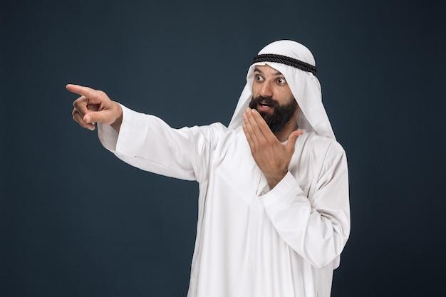 Portrait demi-longueur d'homme d'affaires saoudien arabe sur bleu foncé