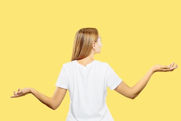 Portrait demi-longueur de la jeune femme caucasienne sur fond de studio jaune. beau modèle féminin en chemise blanche. concept d'émotions humaines, expression faciale. affichage d'un espace vide ou invitant.