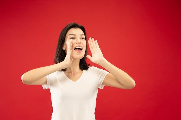 Portrait de demi-longueur de jeune femme caucasienne sur studio rouge