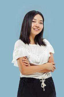 Portrait demi-longueur de la jeune femme coréenne sur l'espace bleu. modèle féminin en chemise blanche. debout et souriant.