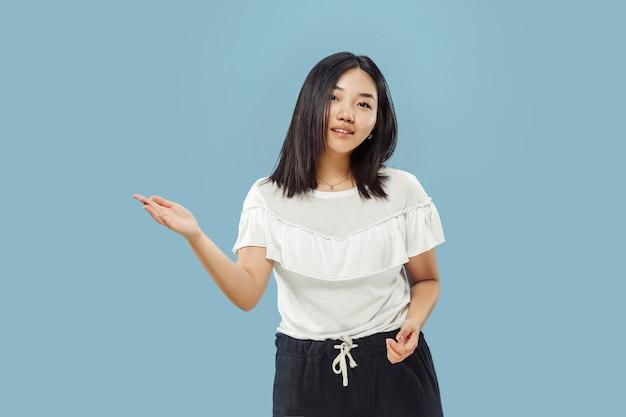 Portrait demi-longueur de la jeune femme coréenne sur l'espace bleu. modèle féminin en chemise blanche. montrer et pointer quelque chose.