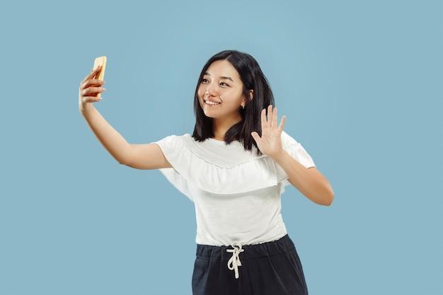 Portrait demi-longueur de la jeune femme coréenne sur fond bleu