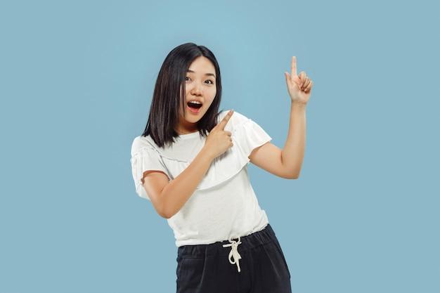 Portrait demi-longueur de la jeune femme coréenne sur studio bleu