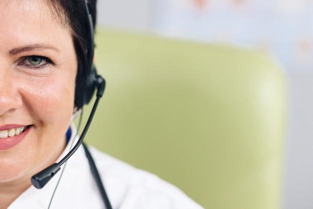 Portrait de demi-visage d'une assistante médicale portant une blouse blanche et un casque regardant l'avant et souriant