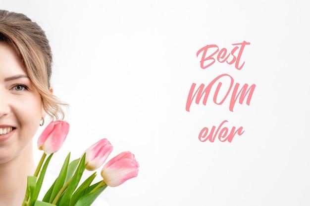 Portrait de demi-visage de jeune femme avec des tulipes roses sur fond blanc et texte best mom ever.