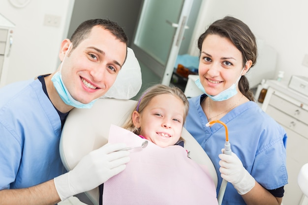 Portrait de dentiste et assistante dentaire avec jeune patient.
