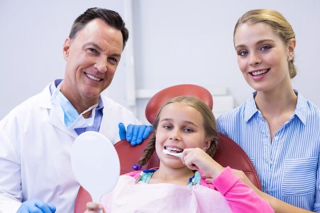 Portrait de dentiste avec jeune patient et sa mère