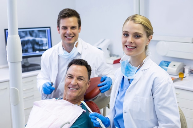 Portrait de dentistes souriants et patient de sexe masculin