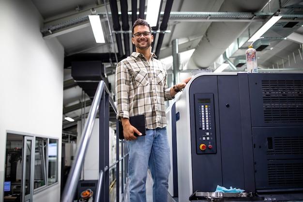 Portrait d'un designer debout près de la machine d'impression et contrôlant la qualité dans l'usine