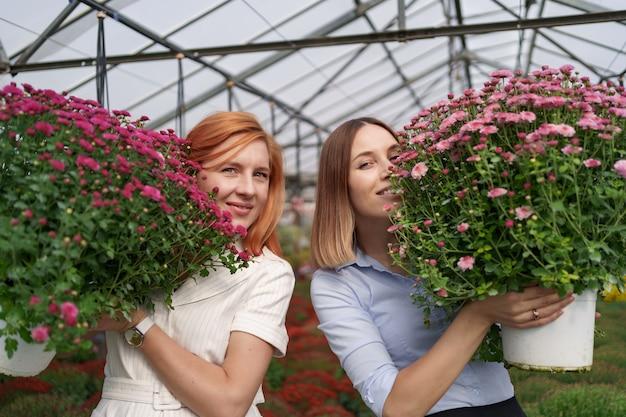 Portrait deux adorables dames posant avec un bouquet de chrysanthèmes roses dans une belle maison verte fleurie avec toit en verre.