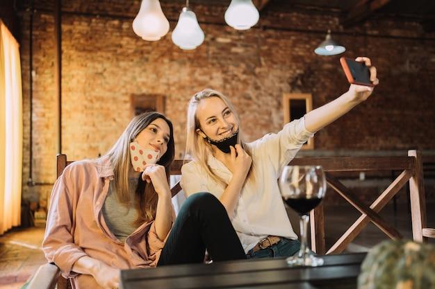 Portrait de deux amies dans un restaurant - deux belles amies caucasiennes portant des masques et prenant un selfie.