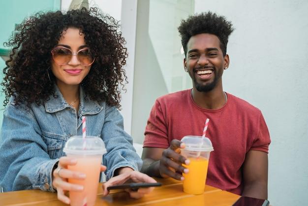 Portrait de deux amis afro s'amuser ensemble et passer du bon temps tout en buvant du jus de fruits frais à l'extérieur à la cafétéria.