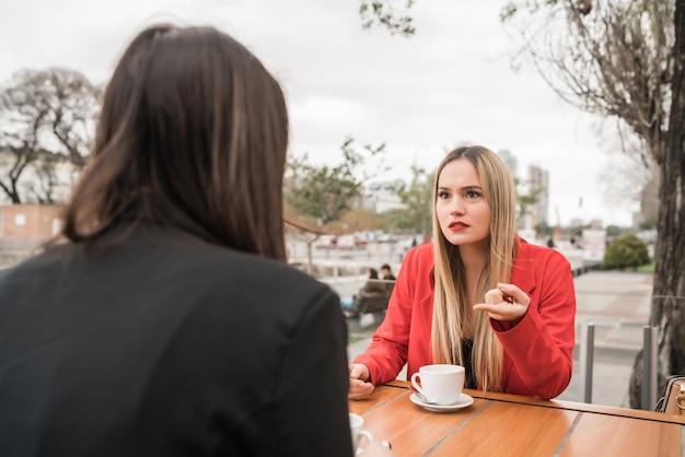 Portrait de deux amis en colère ayant une conversation sérieuse et discutant alors qu'il était assis au café. concept d'amitié.