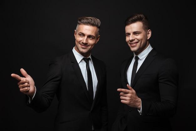 Portrait de deux beaux hommes d'affaires souriants vêtus d'un costume formel pointant du doigt et regardant de côté isolés sur un mur noir