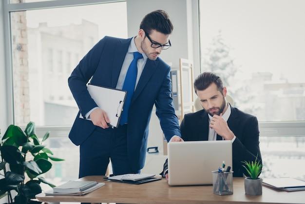 Portrait de deux beaux hommes qualifiés et expérimentés, beaux et occupés, experts en requins, économiste financier, recherchant des données de marché, analysant dans un poste de travail intérieur blanc clair