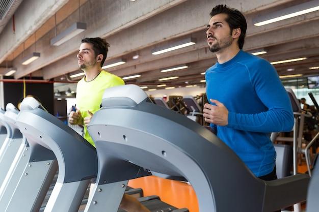 Portrait de deux beaux jeunes hommes faisant du cardio-training en salle de gym.