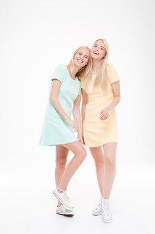 Portrait de deux belles dames riant isolées sur mur blanc