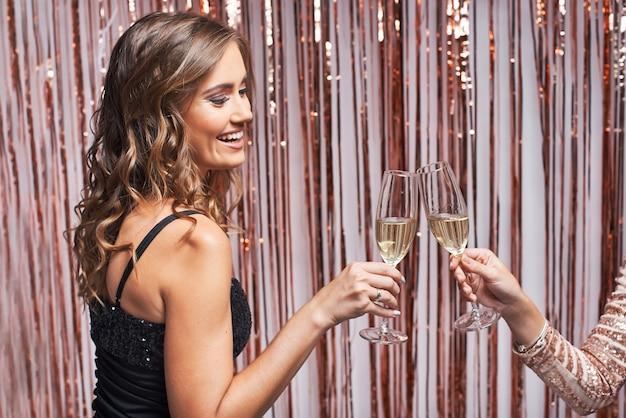Portrait de deux belles femmes élégantes tinter les verres de champagne.