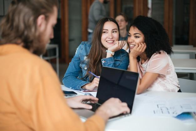 Portrait de deux belles femmes souriantes assis dans la salle de classe et potins tandis que jeune homme travaillant sur son ordinateur portable
