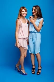 Portrait de deux belles filles sur mur bleu