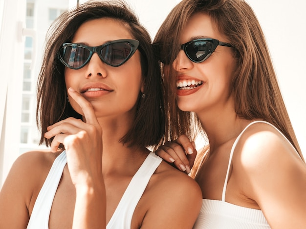 Portrait de deux belles jeunes femmes souriantes en lingerie blanche