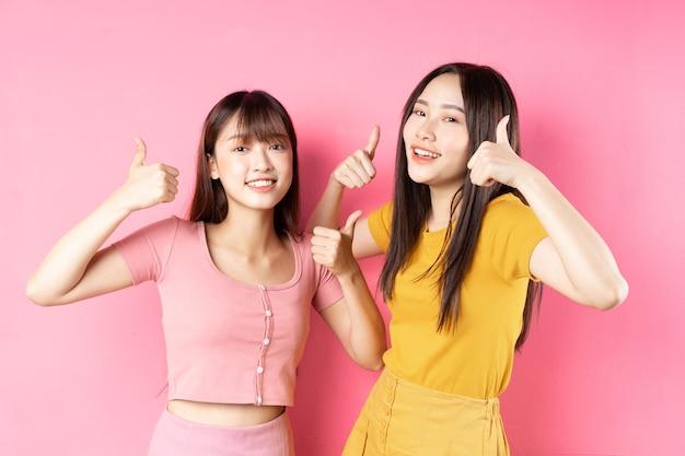 Portrait de deux belles jeunes filles asiatiques posant sur un mur rose