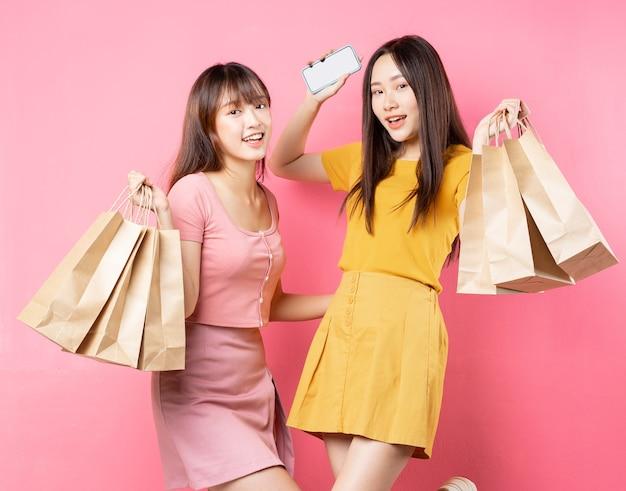 Portrait de deux belles jeunes filles asiatiques tenant de nombreux sacs à provisions sur mur rose