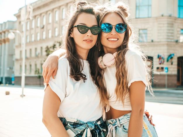 Portrait de deux belles jeunes filles hipster souriantes dans des vêtements de t-shirt blanc d'été à la mode
