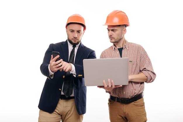 Portrait de deux constructeurs dans des casques de protection orange debout sur fond blanc isolé et regardant l'écran de l'ordinateur portable. discuter du projet de construction
