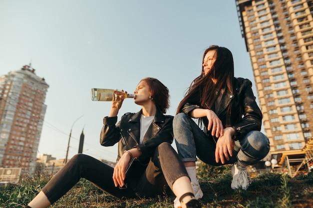 Portrait de deux copines élégantes assis sur une colline sur le ciel