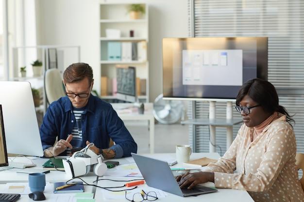 Portrait de deux développeurs informatiques concevant un logiciel de réalité virtuelle tout en travaillant avec des ordinateurs au bureau, espace de copie